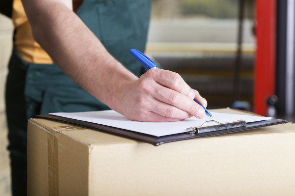 Close-up of a man's hand signing delivery document
